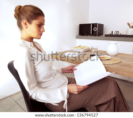 beautiful relaxed young woman at the kitchen counter - Indoor - stock photo