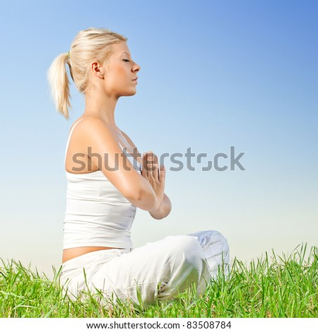 Beautiful relaxed young woman meditating outdoors. - stock photo