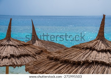 beautiful relaxing place on Red sea in Sinai, closeup of beach umbrellas - stock photo