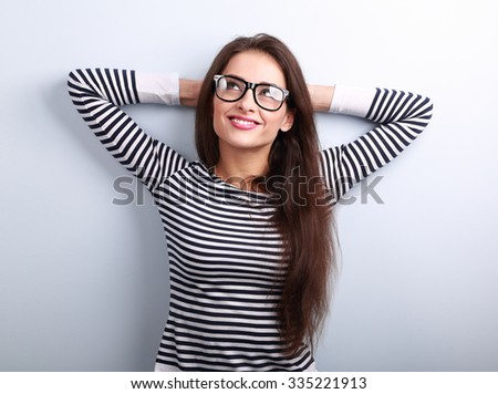 Beautiful relaxing woman in glasses looking up with thinking look on blue background with empty copy space - stock photo