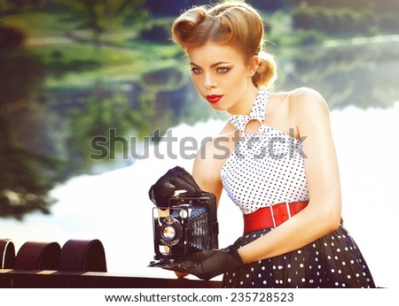 beautiful retro girl in vintage clothing with vintage camera in hand near the lake - stock photo