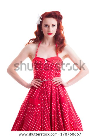 Beautiful retro pin-up girl with red polka dot dress - stock photo