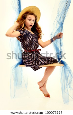 Beautiful retro style portait of nine year old girl in dress and summer hat on swing over white. - stock photo