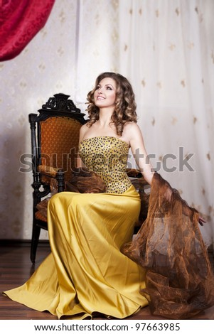 beautiful rich romantic woman in golden dress sitting and smile in luxurious vintage-style retro interior with blond healthy glossy hair. Evening - night. Fashion style shot - stock photo