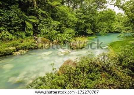 Beautiful rio celeste flows through the Tenorio National Park in Costa Rica. - stock photo