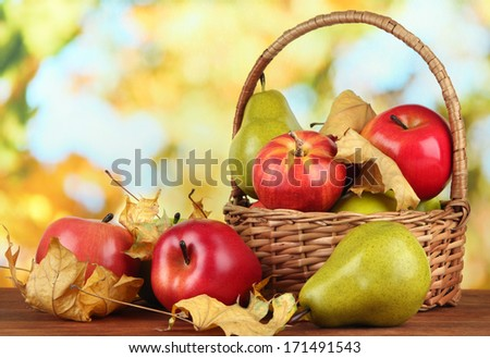 Beautiful ripe apples and pears with yellow leaves in basket on table on bright background - stock photo