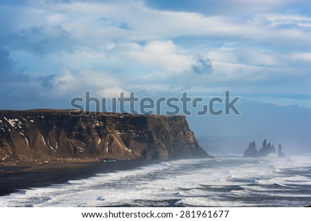 Beautiful rock formation on a black volcanic beach at Cape Dyrholaey, the most southern point of Iceland. - stock photo