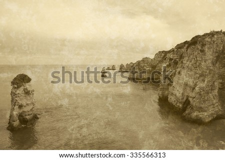 Beautiful rock formations, stone arches and caves at Dona Ana Beach and sailing boats on horizon (Lagos, Algarve coast, Portugal) in the evening light. Retro aged sepia photo with scratches. - stock photo