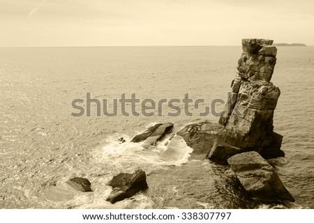 Beautiful rocks in water. Atlantic ocean coast near Peniche (Portugal). Aged photo. Sepia. - stock photo