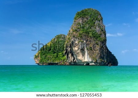 Beautiful rocky island over blue sky - stock photo
