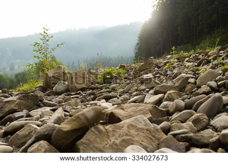 Beautiful rocky mountain landscape. Stones and boulders strewn shore of a mountain river. Photo for Natural magazines, posters, backdrops and websites. - stock photo