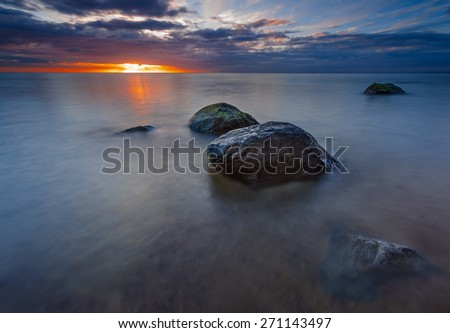 Beautiful rocky sea shore with driftwood trees trunks at sunrise or sunset. Baltic sea shore - stock photo