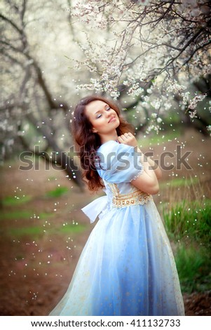 Beautiful romantic girl standing in blooming garden under the flying snow of white petals. Smiling and dreaming princess in fairy dress on blossom orchard. Happy day. Fairy tale and fantasy work. - stock photo