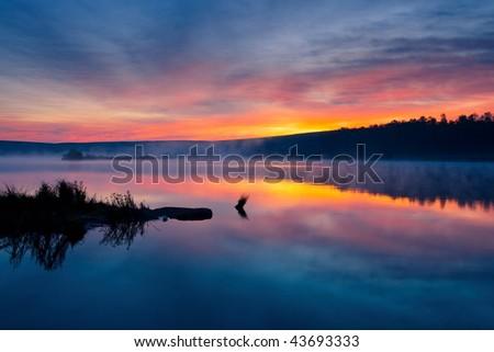 Beautiful romantic sunset over a calm lake - stock photo