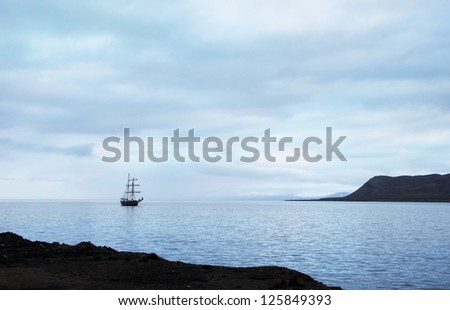 Beautiful romantic view, Sailing ship docked at Longyearbyen port against the background of blue cloudy sky at morning in Advent Bay, Spitsbergen archipelago (Svalbard island), Norway, Greenland Sea  - stock photo