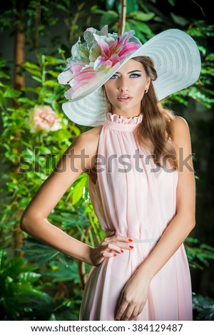 Beautiful romantic woman in light dress and elegant hat posing in a blooming garden. Beauty, fashion.  - stock photo