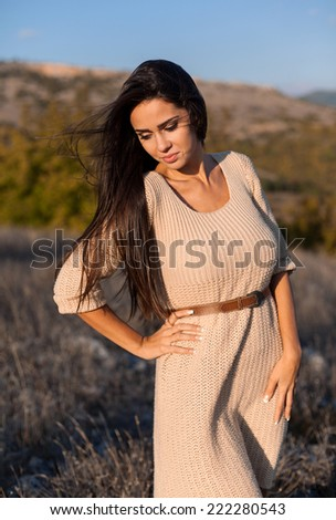Beautiful romantic young woman outdoors. Beautiful young woman wearing fashion autumn clothes. Portrait in a autumn scenery.  - stock photo