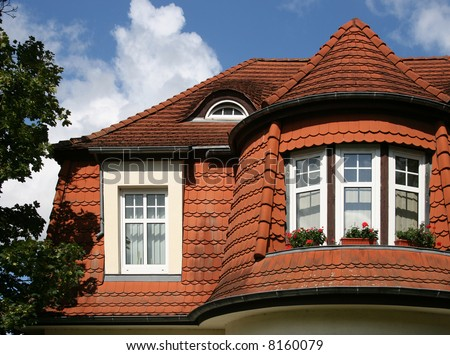 Beautiful roof of a city house with red roofing tiles - stock photo