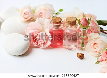 Beautiful rose flowers essential oils white stones spa background empty space - stock photo