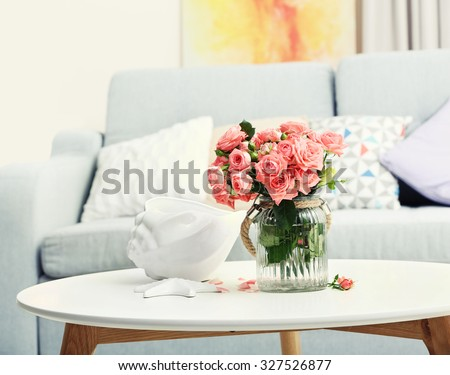 Beautiful rose in vase on table in room  - stock photo