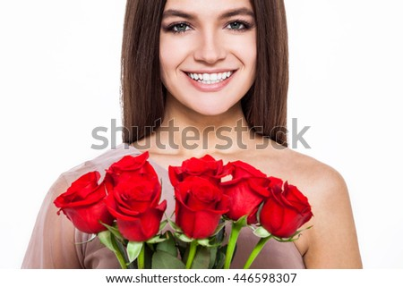 Beautiful roses for beautiful women. Cropped shot of an attractive young woman hold bunch of red roses and smiling into camera while isolated on white. - stock photo