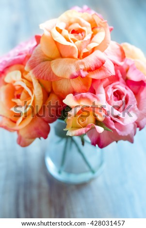 Beautiful roses in a jar on a wooden table. Vintage color post processed. Shallow depth of filed - stock photo