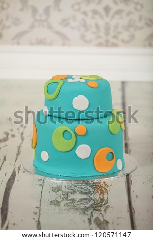Beautiful round double tier blue green and orange polka dot birthday party cake on vintage wallpaper background and distressed white washed wooden floor - stock photo