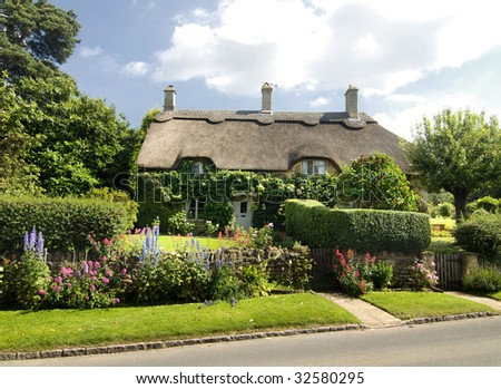 Beautiful rural cottage with thatched roof in the Cotsworld countryside of England - stock photo