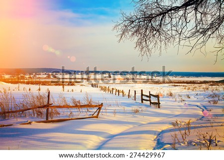 Beautiful rural landscape at sunset in snowy winter - stock photo