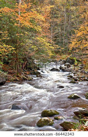 Beautiful rushing water in tree lined stream with boulders and Autumn leaves - stock photo