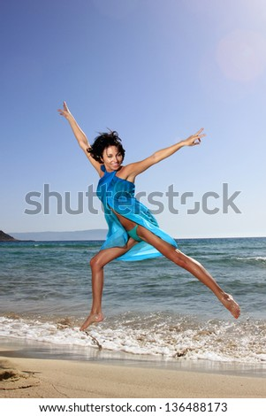 beautiful russian girl at the beach with bikini and blue scarf jumping in the air - stock photo