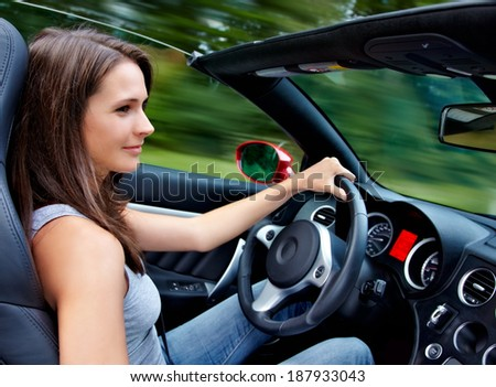 Beautiful 20s driving a roadster - stock photo