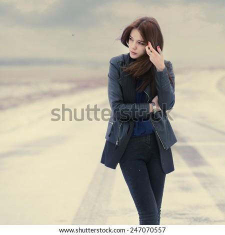 beautiful sad girl in winter on the road - stock photo