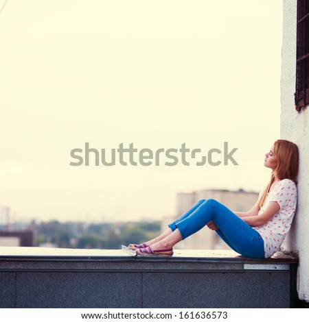 beautiful sad girl sitting on the roof of the house - stock photo