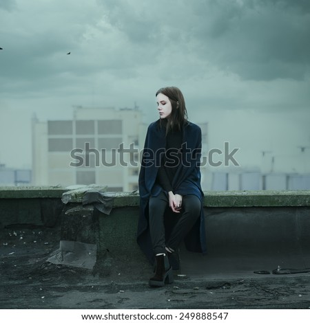 beautiful sad girl sitting on the roof on a cloudy day - stock photo