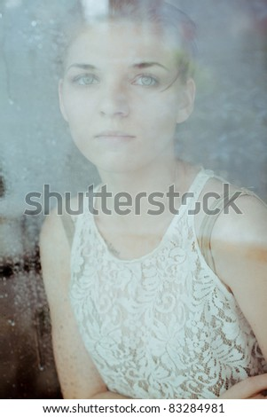 Beautiful sad girl standing at the window watching the rain - stock photo