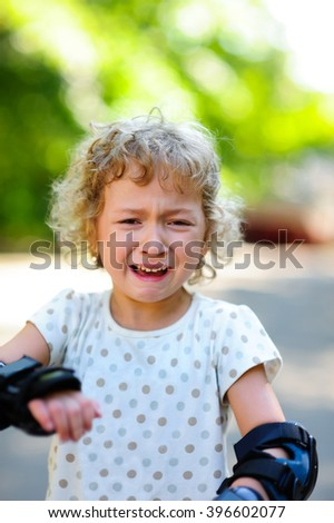 Beautiful sad little girl angry and crying on summer nature background. Close up emotions portrait of crying child. - stock photo