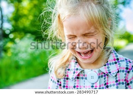 Beautiful sad little girl crying, on summer background. - stock photo