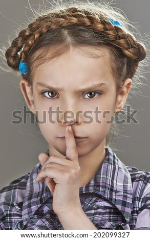 Beautiful sad little girl puts index finger to lips, on gray background. - stock photo