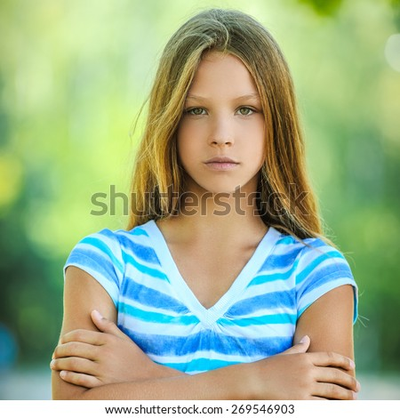 Beautiful sad teenage girl in blue blouse, against green of summer park. - stock photo