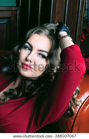 beautiful sad woman with long curly hair lying on the sofa in a luxury interior - stock photo