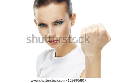 Beautiful sad young woman close-up threatens fist into camera, isolated on white background. - stock photo
