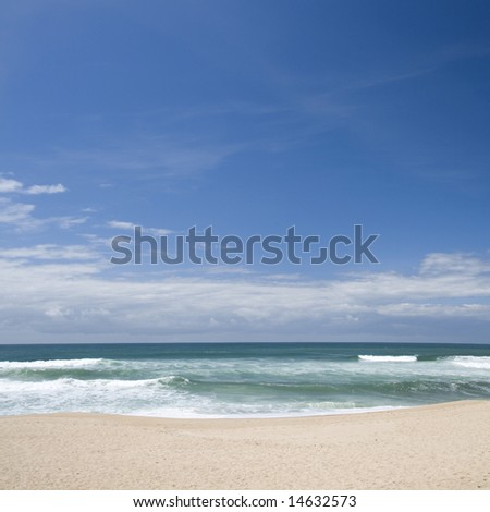 Beautiful sandy beach against blue sky and crystal blue water - stock photo