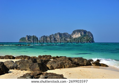 beautiful sandy beach with rocks and distant island on the horizon - stock photo