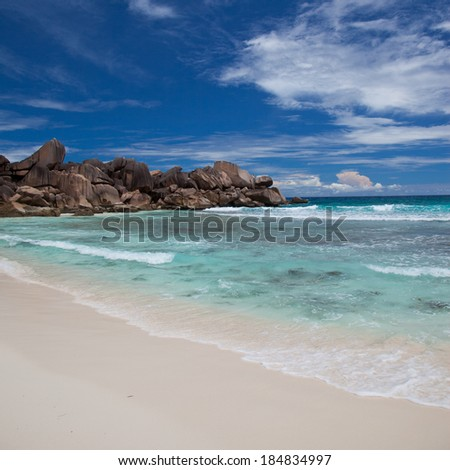 Beautiful sandy tropical beach with a rocky outcrop at the end and calm azure blue ocean under a cloudy sunny blue sky for a perfect vacation getaway - stock photo