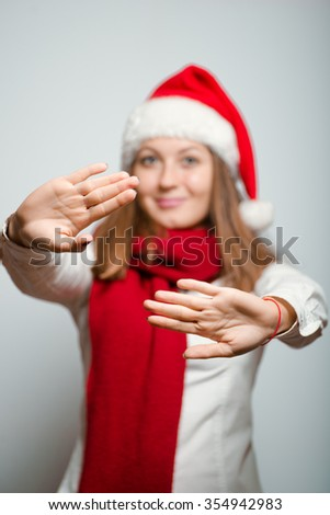 Beautiful Santa girl showing stop. Christmas hat isolated portrait of a woman on a gray background, studio photo. - stock photo