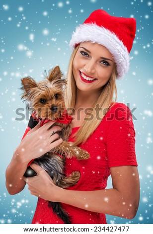 Beautiful santa woman, holding  santa yorkshite terrier, snowfall background - stock photo