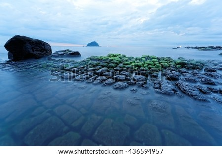 Beautiful scenery of a rocky coast in northern Taiwan on a cloudy morning, with peculiar rock formations on the beach & an island on the distant horizon under dramatic dawning sky ( long exposure ) - stock photo
