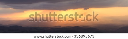 Beautiful scenic hilly landscape panoramic illuminated by brilliant orange afternoon sunlight from behind gray clouds in Minas Gerais, Brazil - stock photo