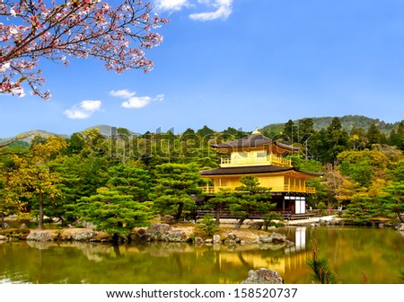 beautiful scenic of the famous golden pavilion at Kinkakuji temple with blue sky and sakura branch, Kyoto, Japan (composition) - stock photo